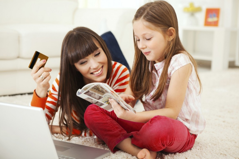 Maminka s dcerou, které si prohlížejí katalog dřevostaveb.