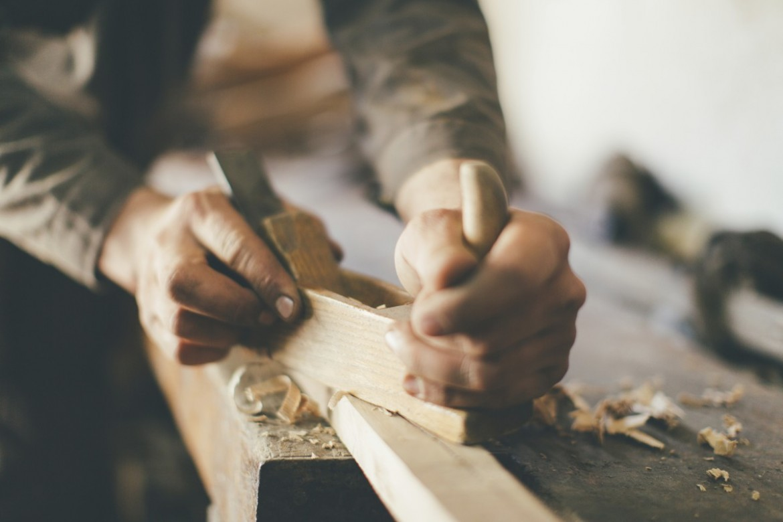 Ruce opotřebovávající dřevo ručním hoblíkem